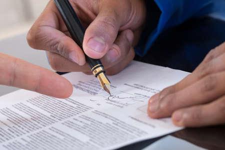 Foto de Detail of a man signing a paper Male finger showing where to sign - Imagen libre de derechos