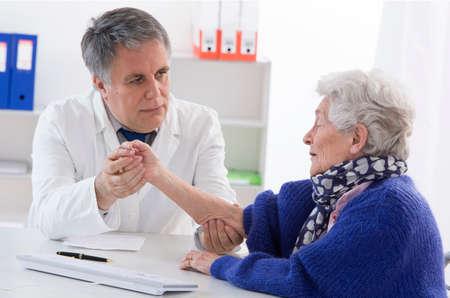 Photo pour Doctor checking elder female patient - image libre de droit