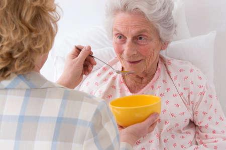 Photo pour Female caregiver serving dinner  to senior woman at nursing home - image libre de droit