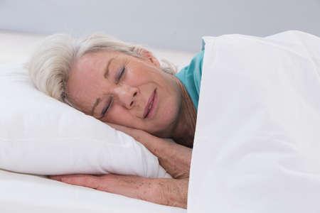 Foto per senior woman sleeping on bed - Immagine Royalty Free
