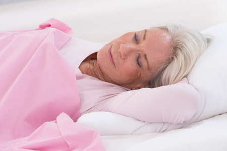 Foto per senior woman sleeping on bed - Immagine Royalty Free