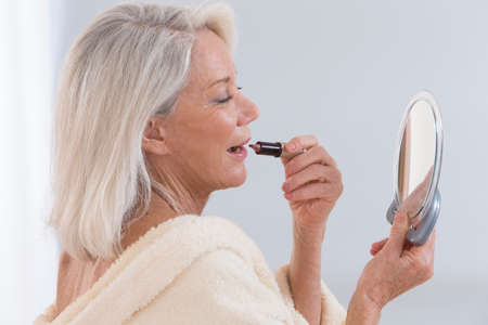 Foto für Senior Woman applying lipstick while looking in her mirror - Lizenzfreies Bild