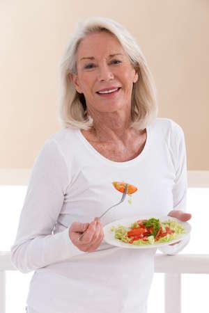 Photo pour Senior woman eating a healthy salad at the kitchen - image libre de droit