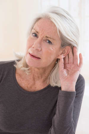 Photo pour Elderly woman with hardness of hearing listening - image libre de droit