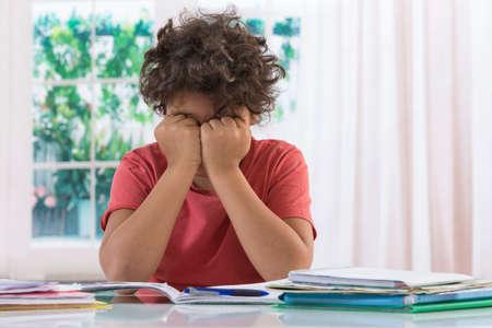 Foto de Young boy drifts from his concentration while studying - Imagen libre de derechos