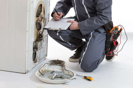 Photo pour Male Technician repairing Washing Machine and Dryer - image libre de droit