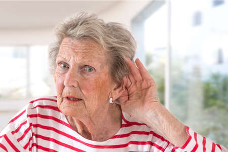 Foto de Elderly lady with hearing problems due to ageing holding her hand to her ear as she struggles to hear, profile view on large windows background - Imagen libre de derechos