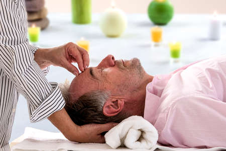 Photo pour Side view of relaxed senior man receiving forehead massage in spa beaty salon - image libre de droit