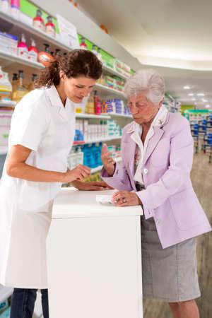 Foto de medicine, pharmaceutics, health care and people concept - happy pharmacist showing drug lnstruction to senior woman customer at drugstore - Imagen libre de derechos