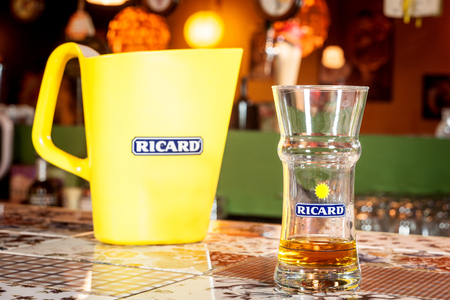 Foto de MARSEILLE, FRANCE - MARCH 15, 2018: Close up of a Ricard jug and a water bottle with its logo. Ricard is a pastis, anise and licorice flavored aperitif typical from Southern France - Imagen libre de derechos
