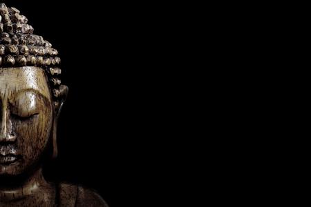 Foto de Wooden buddha statue on table shot in studio - Imagen libre de derechos