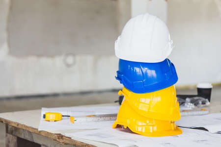 Foto de The white, blue and yellow safety helmet stacking on table with the blueprint and measuring tools  at construction site for Engineer, foreman and worker. Safety first concept. - Imagen libre de derechos