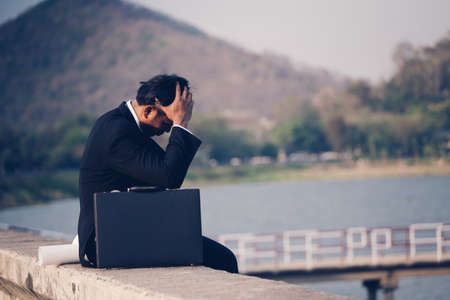 Photo for Back view of tired or stressed businessman in a suit with a briefcase and sitting on concrete of reservoir with mountains view. Unemployed businessman concept. - Royalty Free Image