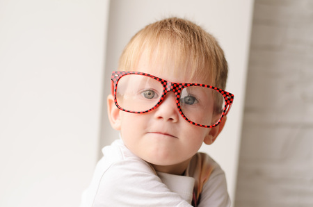 Photo for Blond boy in red glasses close up sitting on a background of a white brick wall - Royalty Free Image