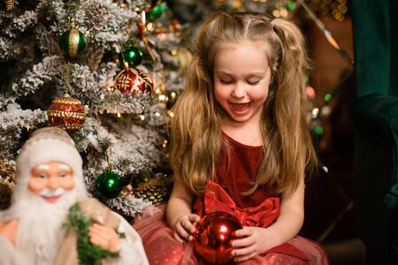 Photo for Portrait of beautiful girl near festive Christmas tree trimmed with balls, against background of mirror, bokeh from lights of garlands - Royalty Free Image