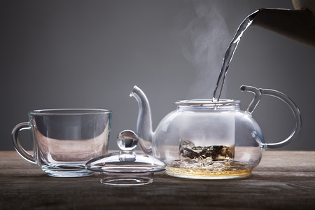 Photo for poured from a teapot cup of tea on a wooden table - Royalty Free Image