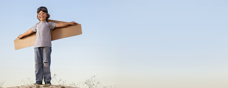 Foto de Happy boy with cardboard boxes of wings against the sky dream of flying - Imagen libre de derechos