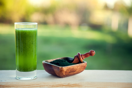 Foto de Green smoothie with spirulina on wood background - Imagen libre de derechos
