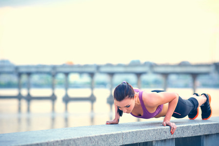 Foto de Sport, fitness, people and weight loss concept - beautiful sporty young woman over city waterside background - Imagen libre de derechos