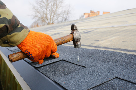 Photo pour Worker hands installing bitumen roof shingles. Worker Hammer in Nails on the Roof. Roofer is hammering a Nail in the Roof Shingles. - image libre de droit