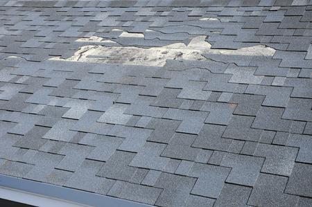 Foto de A close up view of shingles a roof damage. Roof Shingles - Roofing. - Imagen libre de derechos