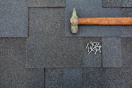 Photo for Close up view on Asphalt Roofing Shingles Background. Roof Shingles - Roofing. Asphalt Roofing Shingles Hammer and Nails - Royalty Free Image
