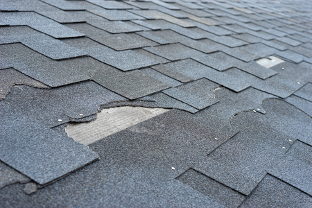 Photo for Ð¡lose up view of asphalt shingles roof damage that needs repair. - Royalty Free Image