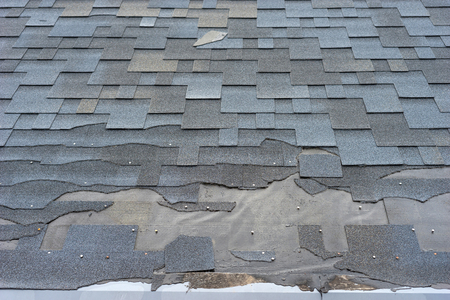 Photo for Ð¡lose up view of bitumen shingles roof damage that needs repair. - Royalty Free Image