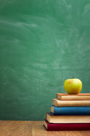 Photo pour School books with apple on desk over green  school board background - image libre de droit
