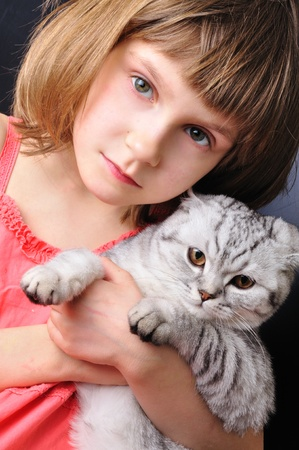 beaituful child girl with her pet cat together