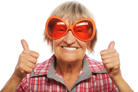 Foto de Senior woman wearing big sunglasses doing funky action isolated on white background - Imagen libre de derechos