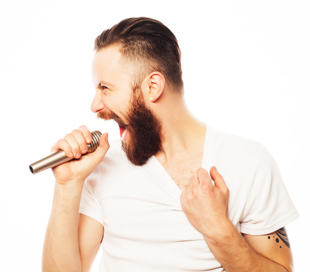 Photo for Life style concept: a young man with a beard wearing a white shirt holding a microphone and singing.Isolated on white. - Royalty Free Image