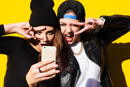 Foto de Two teenage girls friends in hipster outfit outdoors make selfie on a phone. - Imagen libre de derechos
