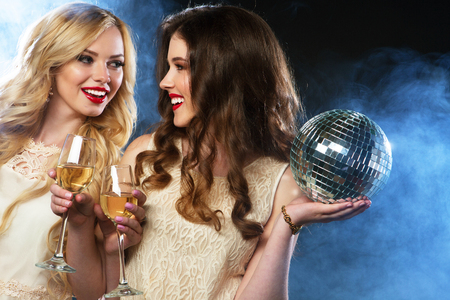 Photo for two beautiful young women with wine glasses and disco ball. - Royalty Free Image