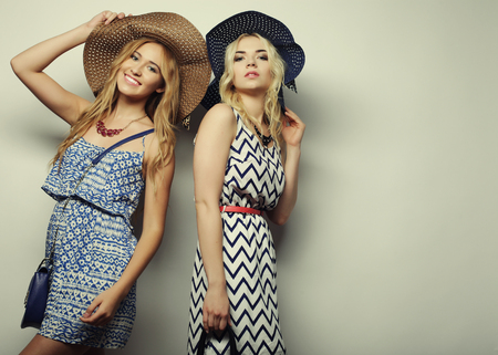 Foto de fashion concept: two sexy young women in summer fashion dress and straw hats, studio background - Imagen libre de derechos
