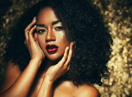 Foto de young elegant african american woman with afro hair. Glamour makeup. Golden Background. - Imagen libre de derechos