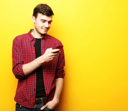 Foto de Happy young man talking on cell phone over yellow background - Imagen libre de derechos