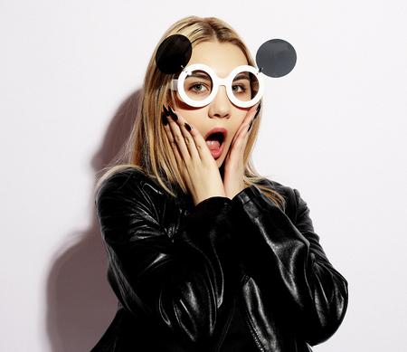 Foto de Attractive surprised young woman wearing creative sunglasses, beauty, people and fashion concept. - Imagen libre de derechos