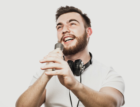 Photo for Young bearded man with headphones and microphone over white background - Royalty Free Image
