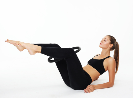 Photo pour Young sporty woman with perfect body having a training with pilates ring over white background - image libre de droit