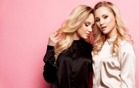 Photo pour Two beautiful young women in casual clothes posing over pink background. - image libre de droit