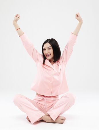 Photo for beautiful brunette woman dressed in pink pajamas sitting on the floor - Royalty Free Image