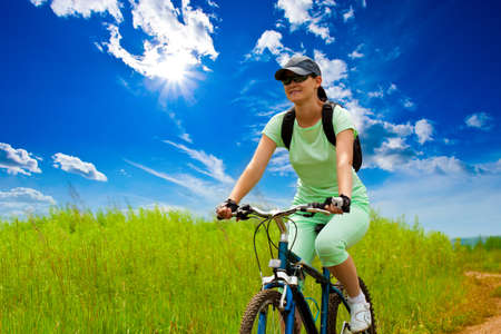 woman with bike on green field under blue skies
