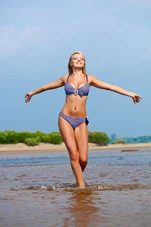 beautiful woman walking on water wearing bikini