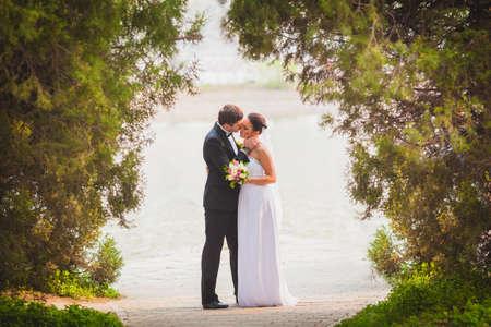 Foto de bride and groom outdoors park under trees arc - Imagen libre de derechos