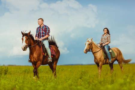 Photo pour loving couple riding on horses across the field over cloudy skies - image libre de droit