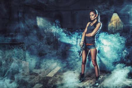 Photo pour sexy brutal woman standing on factory ruins and holding handgun - image libre de droit