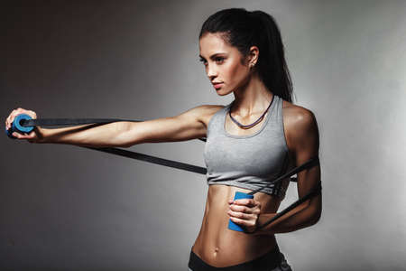 Foto de brunette athletic woman exercising with rubber tape - Imagen libre de derechos