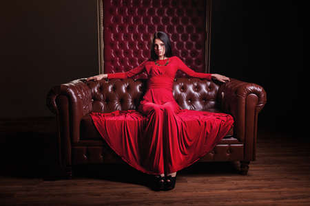 Photo pour elegant sensual young brunette woman in red dress sitting on leather sofa and looking at camera - image libre de droit