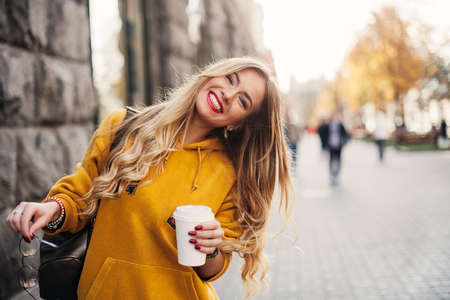 Foto de Stylish happy young woman wearing boyfrend jeans, white sneakers bright yellow sweetshot.She holds coffee to go. portrait of smiling girl in sunglasses and bag - Imagen libre de derechos
